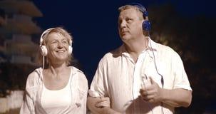 Hoger paar die aan muziek tijdens nachtgang luisteren stock videobeelden