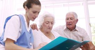 Hoger paar die aan verpleegster spreken stock footage