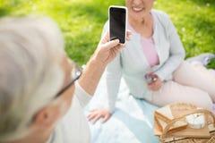 Hoger paar die beeld nemen door smartphone bij park stock afbeelding