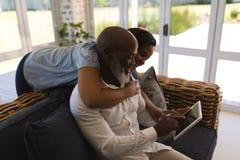 Hoger paar die digitale tablet in woonkamer thuis gebruiken royalty-vrije stock foto