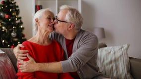 Hoger paar die en bij Kerstmis koesteren kussen stock video