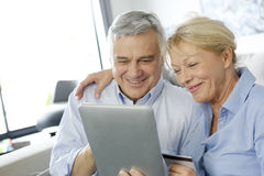 Hoger paar die gebruikend tablet glimlachen stock afbeelding