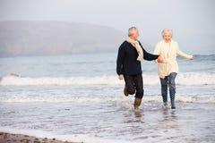 Hoger Paar die langs de Winterstrand lopen Stock Fotografie