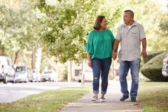 Hoger Paar die langs Handen de In de voorsteden van de Straatholding lopen royalty-vrije stock fotografie
