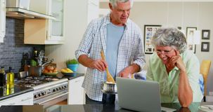 Hoger paar die laptop met behulp van terwijl het koken in keuken 4k stock video