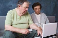 Hoger paar die met creditcard rekeningen online betalen stock foto