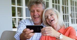 Hoger paar die mobiele telefoon op de portiek 4k met behulp van stock video