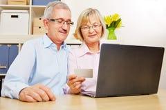 Hoger paar die online bankwezen doen bij computer stock foto's