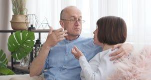 Hoger paar die op bank thuis bespreken stock videobeelden