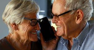 Hoger paar die op mobiele telefoon in keuken 4k spreken stock footage