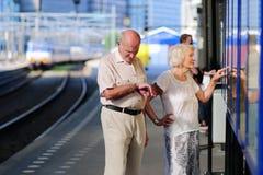 Hoger paar die op trein bij station wachten Stock Foto's
