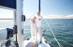Hoger paar die op zeilboot of jacht koesteren in overzees Stock Foto