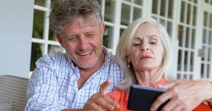 Hoger paar die over mobiele telefoon op de portiek 4k bespreken stock videobeelden