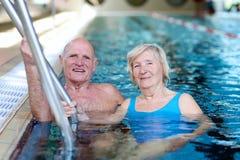 Hoger paar die in pool zwemmen Stock Afbeeldingen