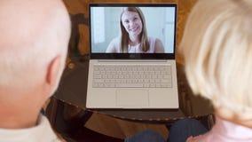 Hoger paar die thuis videopraatje via boodschappersapp vraag op laptop met hun dochter hebben in het buitenland stock videobeelden