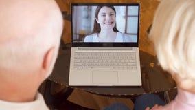 Hoger paar die thuis videopraatje via boodschappersapp vraag op laptop met hun dochter hebben in het buitenland stock video