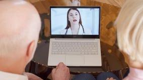 Hoger paar die thuis videopraatjeoverleg via boodschappersapp vraag op laptop met arts hebben stock videobeelden