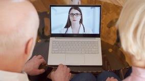 Hoger paar die thuis videopraatjeoverleg via boodschappersapp vraag op laptop met arts hebben stock footage