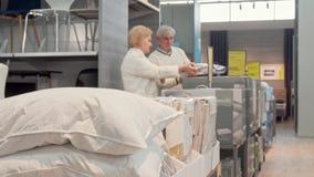 Hoger paar die voor nieuwe comfortabele slaaphoofdkussens bij meubilairopslag winkelen stock footage