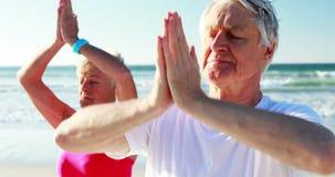 Hoger paar die yoga doen bij strand stock footage
