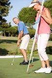 Hoger Paar Golfing op de Cursus van het Golf Royalty-vrije Stock Afbeelding