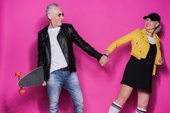 Hoger paar in leerjasjes die met skateboard stellen en handen op roze houden stock foto