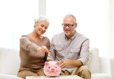 Hoger paar met geld en spaarvarken thuis Stock Foto's