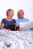 Hoger Paar met Tablet en Krant in Bed stock foto's
