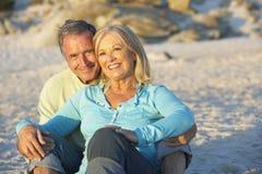 Hoger Paar op de Zitting van de Vakantie op Zandig Strand stock afbeeldingen