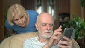 Hoger Paar thuis Echtgenoot die smartphone gebruiken Vrouw die op haar echtgenoot van zijn schouder spioneren stock video