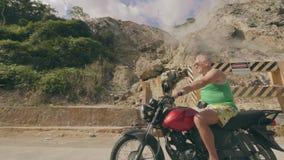 Hoger personenvervoer op motorfiets voorbij bergen met stoom van de hete lentes Volwassen mens die op motor binnen reizen stock videobeelden