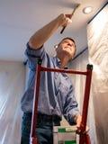 Hoger volwassen mens het schilderen plafond van keuken Stock Foto