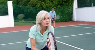 Hoger vrouwen speeltennis in tennisbaan 4k stock video