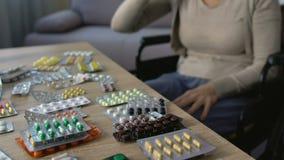 Hoger wijfje in rolstoel die pillen met water nemen, die dosis, verslaving verhogen stock footage