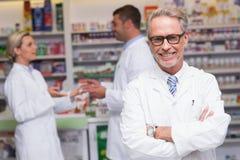 Hogere apotheker die bij camera glimlachen stock afbeeldingen