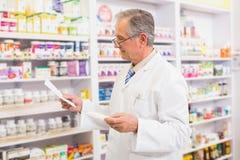 Hogere apotheker die geneeskunde en voorschrift bekijken Royalty-vrije Stock Afbeelding