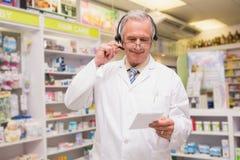Hogere apotheker met het voorschrift van de hoofdtelefoonlezing Stock Fotografie