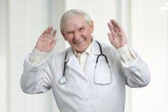 Hogere arts die hard met opgeheven omhoog handen lachen royalty-vrije stock foto