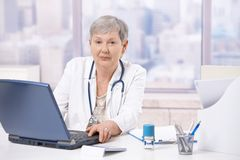 Hogere arts die laptop computer met behulp van Stock Foto