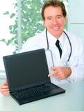 Hogere Arts die Laptop in Zijn Bureau voorstelt Stock Foto