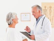 Hogere arts die met zijn zieke patiënt spreekt Royalty-vrije Stock Foto