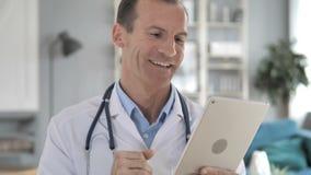 Hogere Arts Discussing met Patiënt via Videopraatje op Tablet stock videobeelden