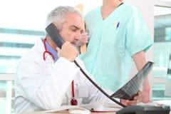 Hogere arts op de telefoon Stock Foto's