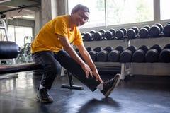Hogere Aziatische sportmens die zijn been in fitness gymnastiek uitrekken ouder mannetje die, het uitwerken, gezonde opleiding, P stock foto's