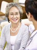 Hogere Aziatische vrouw die aan een medische arbeider spreken stock afbeelding