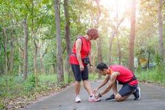 Hogere Aziatische vrouw met de mens of het persoonlijke kant van de trainer bindende schoen in het park stock afbeeldingen