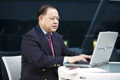 Hogere Aziatische zakenman die laptop PC met behulp van royalty-vrije stock fotografie