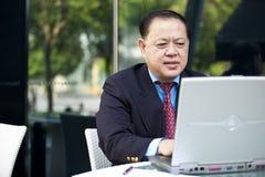 Hogere Aziatische zakenman die laptop PC met behulp van royalty-vrije stock foto's