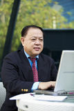 Hogere Aziatische zakenman die laptop PC met behulp van royalty-vrije stock foto