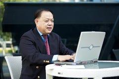 Hogere Aziatische zakenman die laptop PC met behulp van stock afbeelding